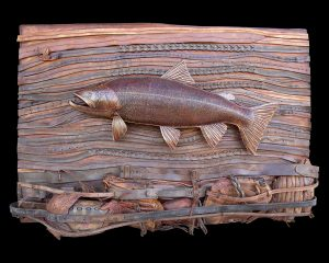 """This River Bed Environment is a one of a kind original hand crafted by Lance Marshall Boen. This three dimensional sculpture is inspired by Lance's passion for fly fishing. Vintage Baseball gloves, hand tooled leaves made of leather, and leather saddle tack form a unique riverbed environment. Serpentine belts and saddle tack are merged together to display the flow of the water current while a 28"""" trout lays eyes on an appetizing mayfly."""