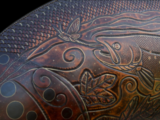 6' Brown Trout Leather Fish Sculpture created by Lance Marshall Boen. Hand tooled imagery of the Trout's lifecycle is depicted within its body. From egg to juvenile fish, including predators and prey tells the story of the Trout's underwater world.