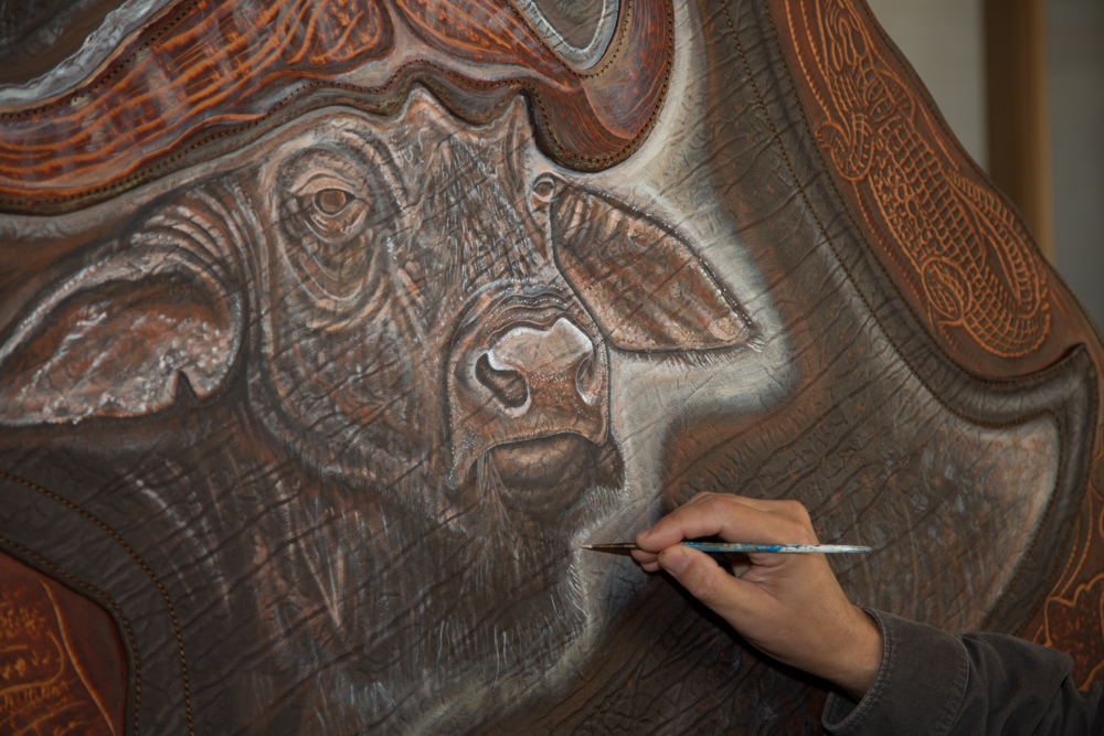 Lance Boen Painting a Cape Buffalo on a Cape Buffalo Hide.