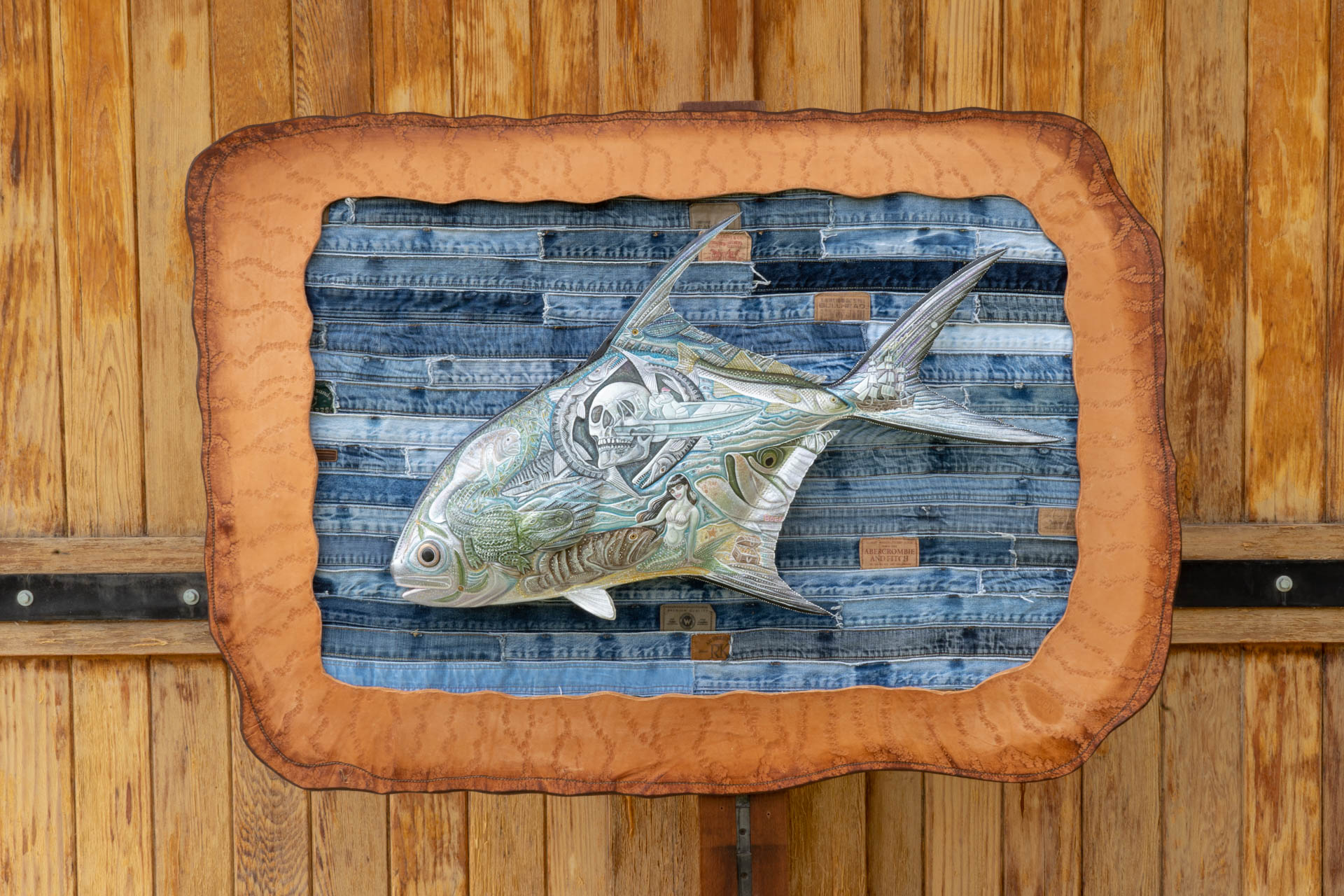 A finely detailed permit fish is mounted on a background of horizontally ripped jeans to create the effect of being in the ocen.