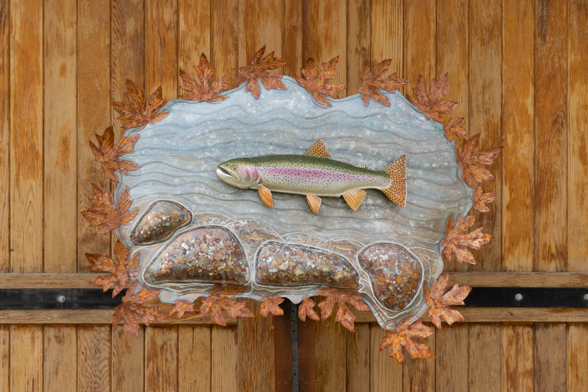 Leather fish sculpture, Autumn Rainbow. A sculpted rainbow trout is mounted on a backdrop of a river flowing behind it and leaves and rocks surrounding the trout.
