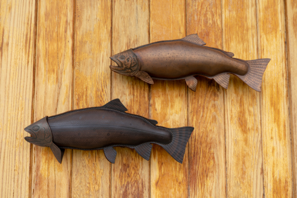 Trout sculpted from leather hang on a wall.