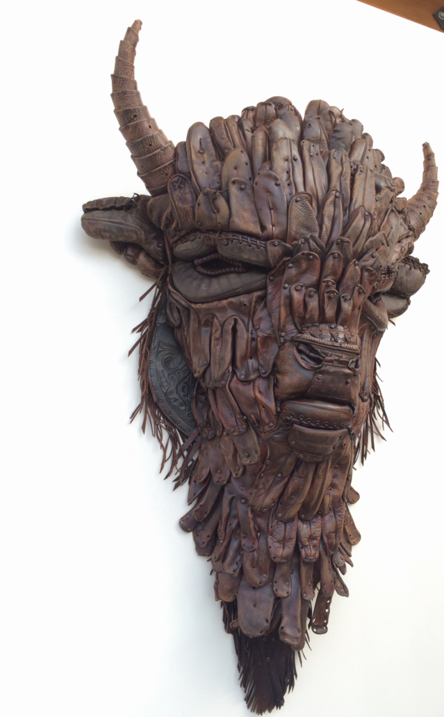 Massive sculpture of a buffalo head mad from vintage baseball gloves.