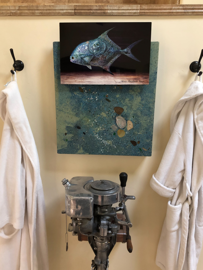 A print of a permit sculpture hangs above an antique outboard motor