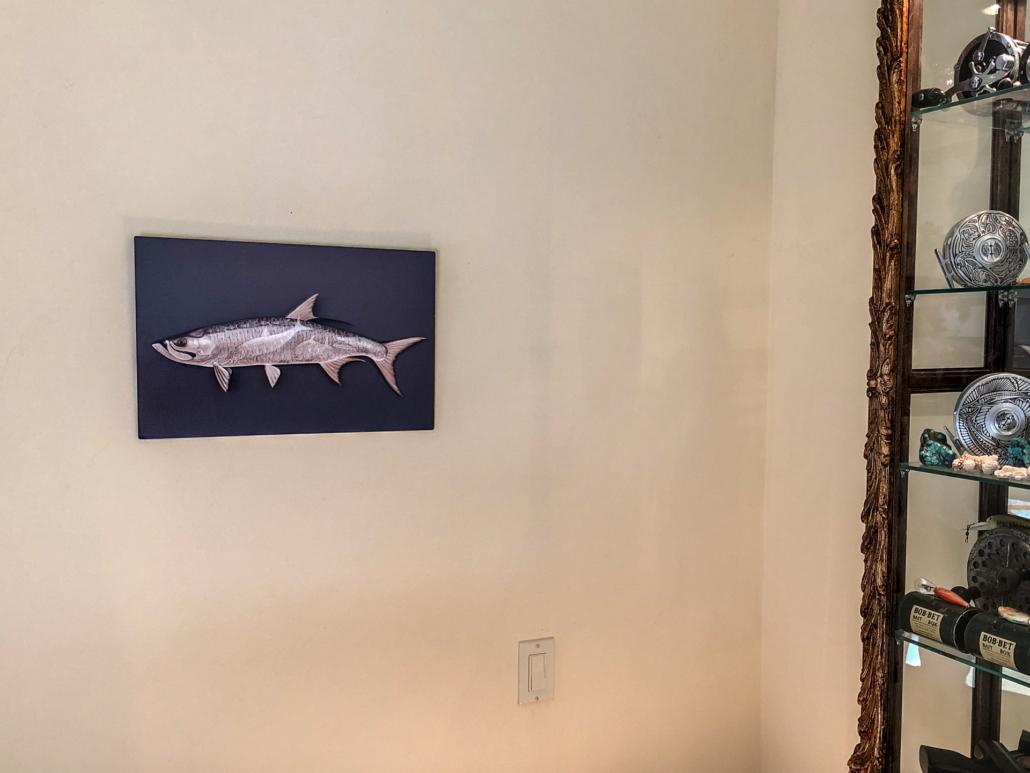 Metal print of a tarpon hangs on the wall