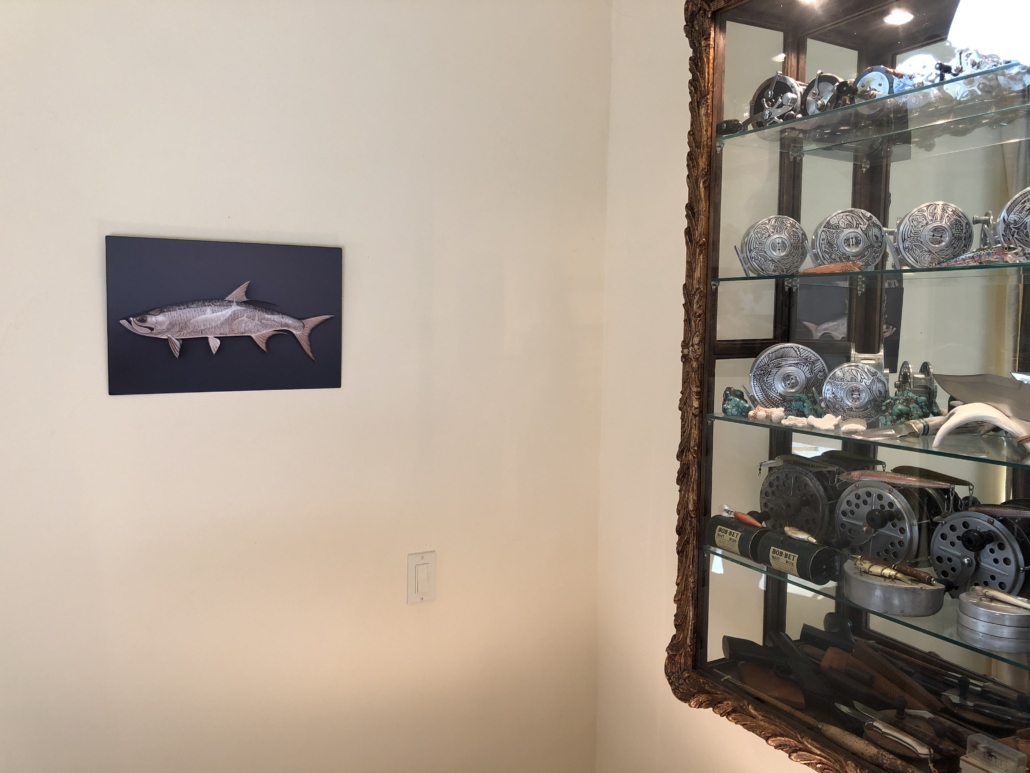 Metal print of a tarpon hangs on the wall